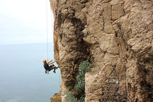 man rappelling on a cliff